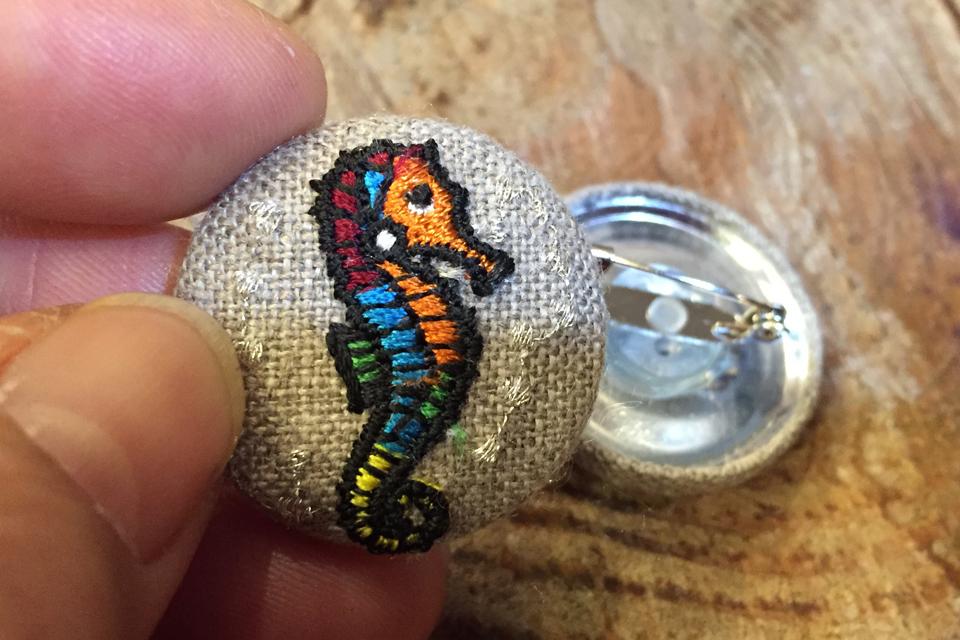 タツノオトシゴの刺繍くるみボタンに安全ピンを取り付けたバッジ