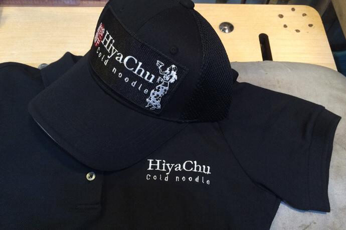 大型ワッペンを貼り付けたキャップと店舗名を『名入れ』刺繍したスタッフユニフォーム