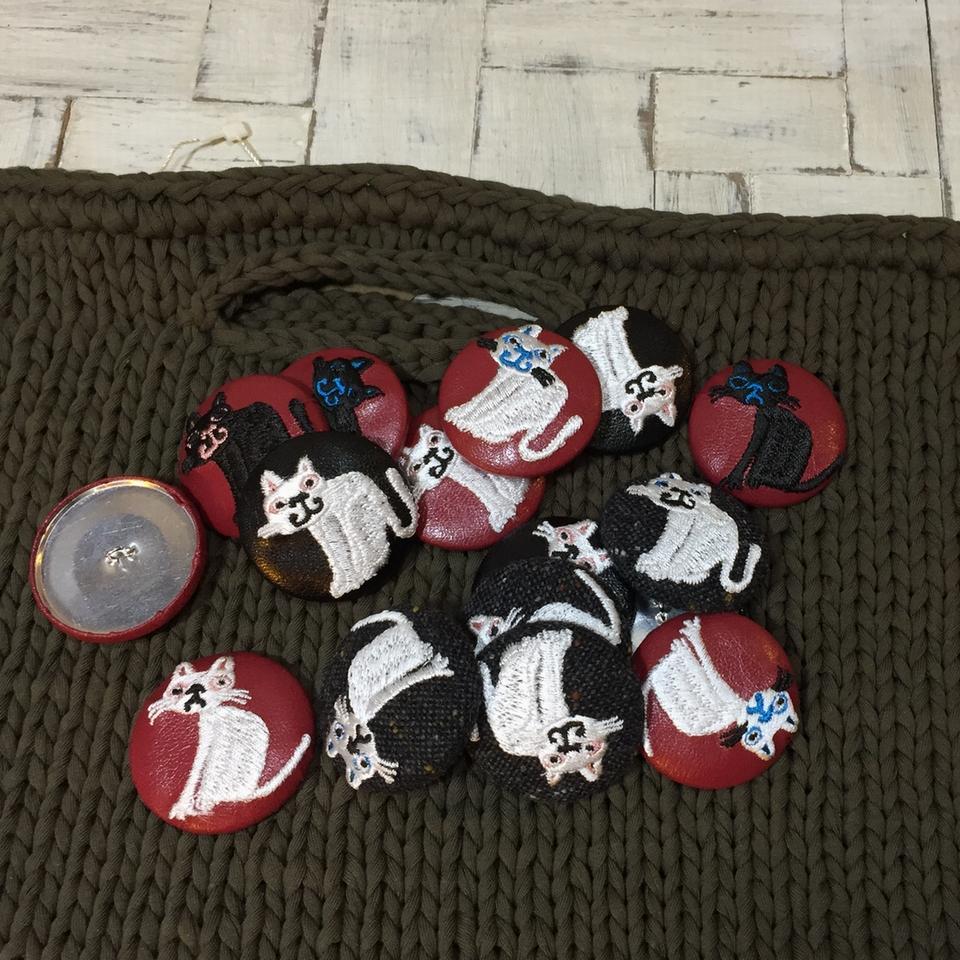 スマイル白黒ネコ刺繍くるみボタン/バックの上に集合