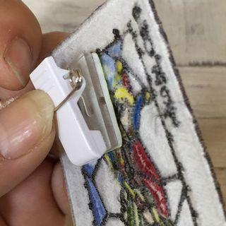 クリップ&安全ピンを取り付けたJOKERのトランプの刺繍ワッペンの背面をアップで見たところ