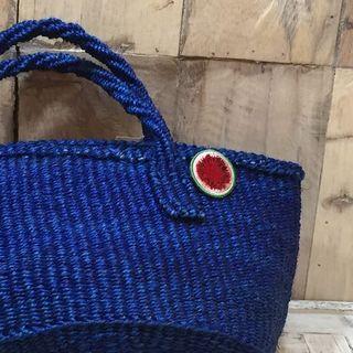スイカのブローチを取り付けた青いバッグ