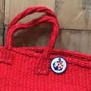 刺繍ブローチを取り付けた赤いバッグ