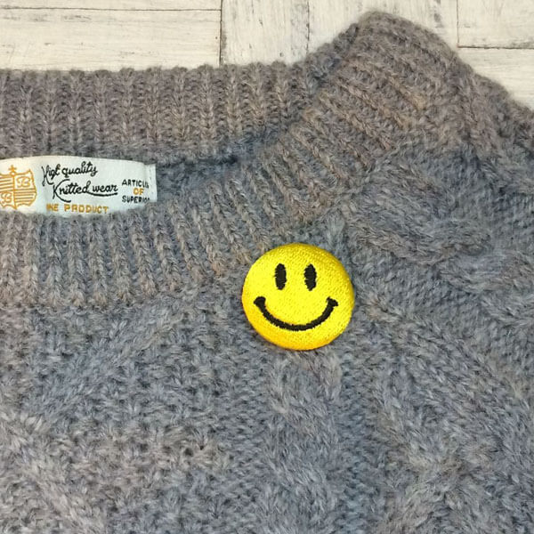 ニコちゃんマーク刺繍くるみボタンMサイズを付けたセーター