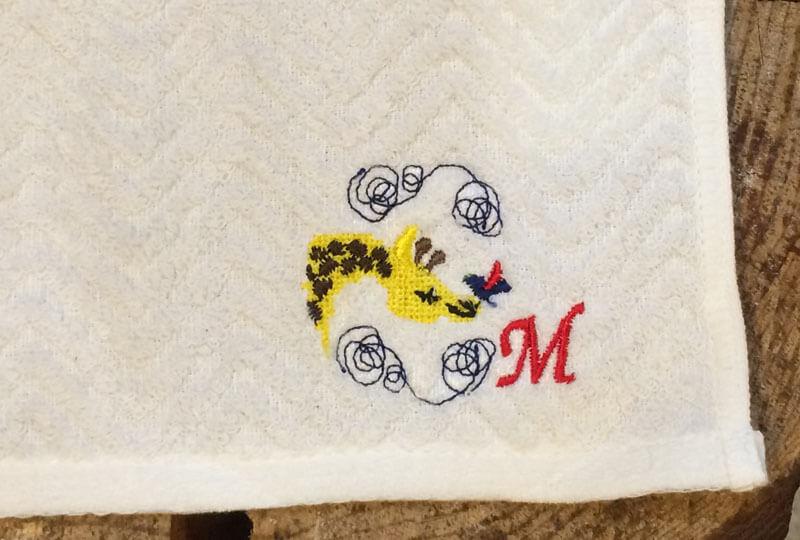 キリンの刺繍図案とイニシャルMを筆記体で刺繍したハンカチプレゼント
