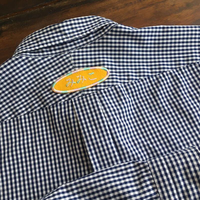 お名前ワッペン/明朝体[だ円Mフェルト]をチェックのシャツの背後へ貼り付けた使用例