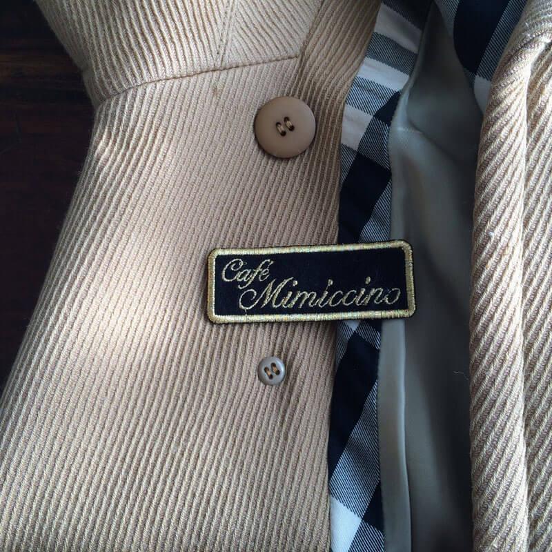 筆記体ネームワッペン[四角形×Mサイズ×黒フェルト]アルファベット・ローマ字をグレーのコートに貼り付けた使用例