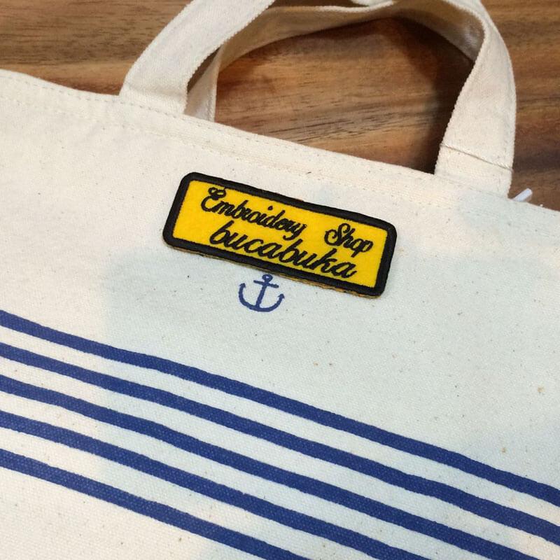 筆記体ネームワッペン[四角形×Mサイズ×黄フェルト]をアンカーバッグへ貼り付けた使用例
