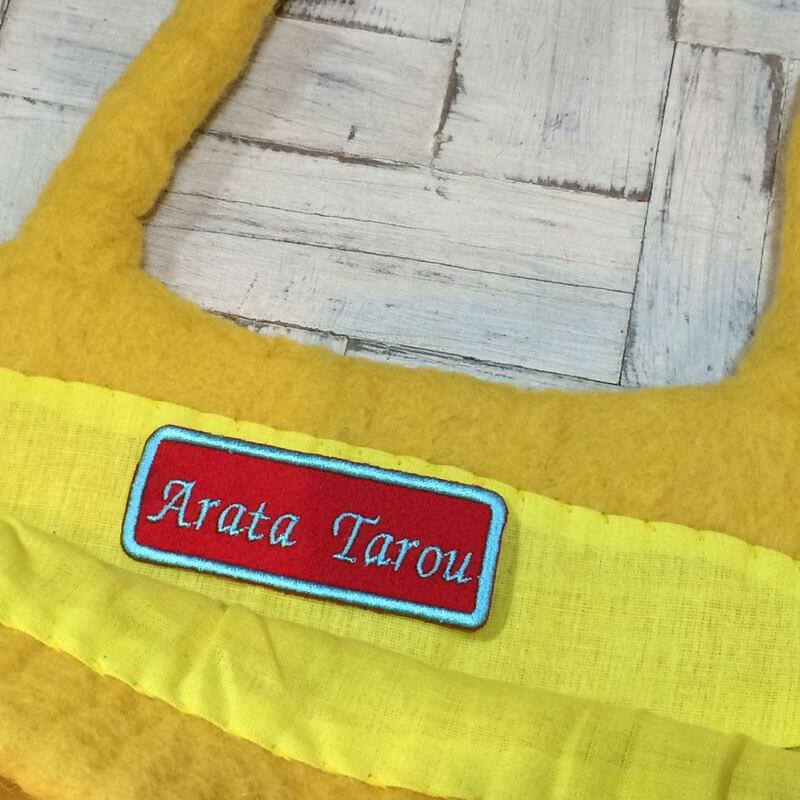 イタリック体ネームワッペン[四角形×Mサイズ×赤フェルト]を黄色いフェルトバッグに貼り付けた使用例